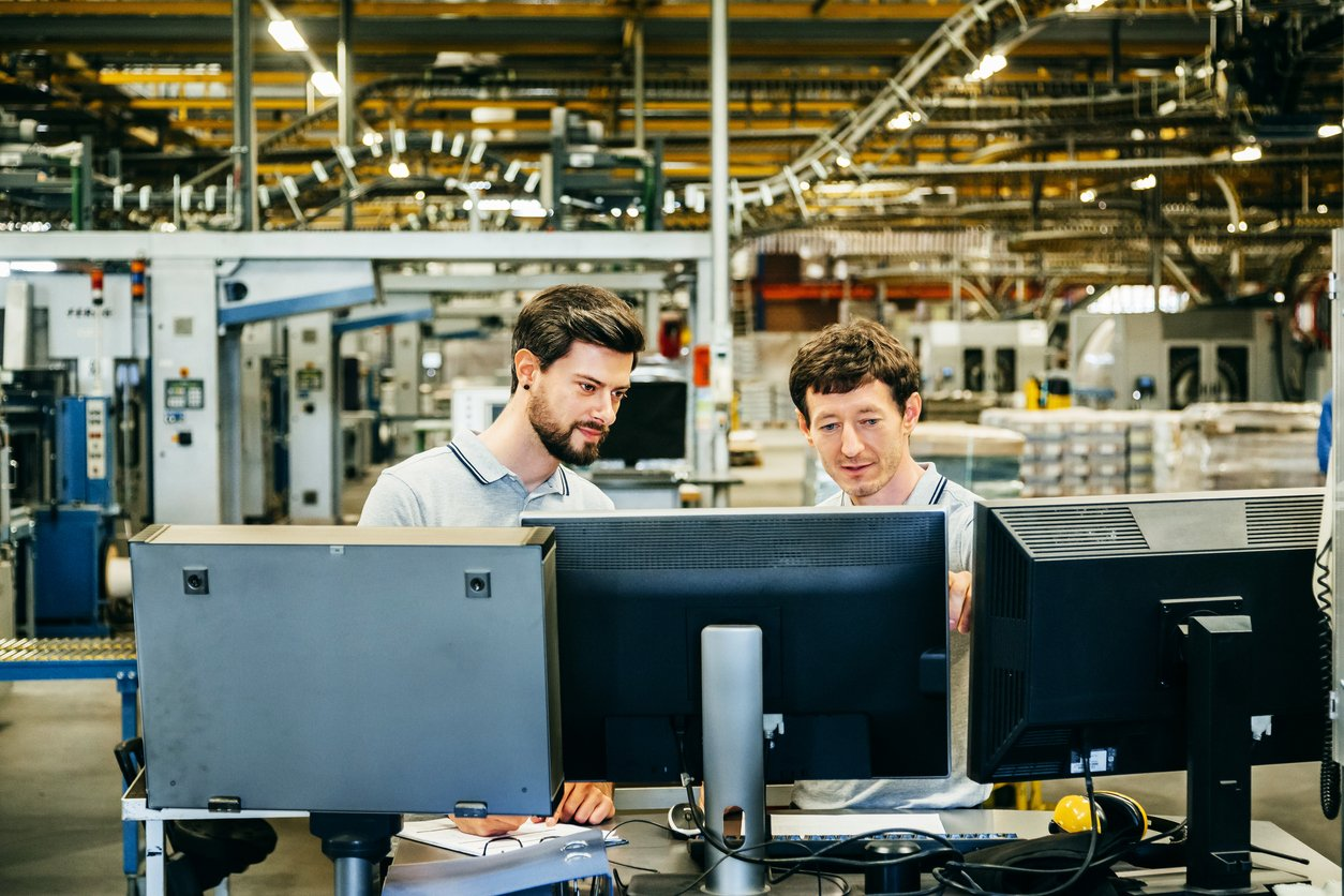 Two engineers standing behind several computer conitors in a huge factory and talking about problems of production line